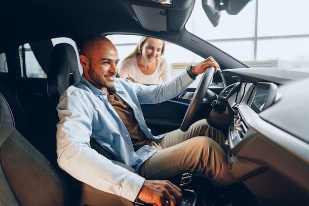 Joyeux jeune couple à l'intérieur d'une nouvelle voiture qu'ils vont acheter