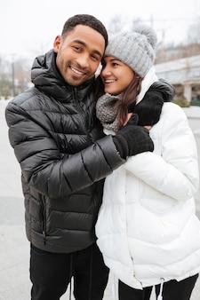 Joyeux jeune couple multiethnique debout ensemble à l'extérieur