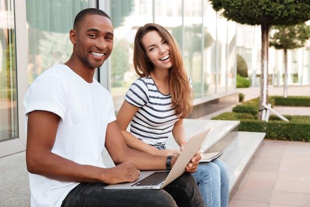Joyeux jeune couple multiethnique utilisant un ordinateur portable et riant à l'extérieur