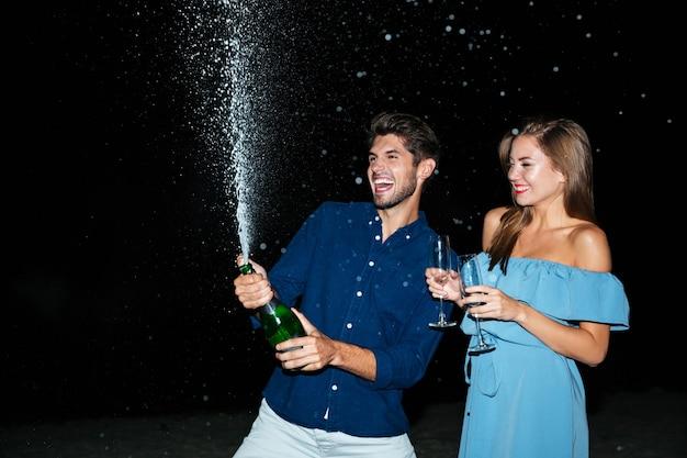Joyeux jeune couple ouvrant une bouteille de champagne et s'amusant la nuit