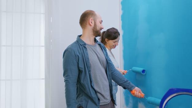 Joyeux jeune couple peignant ensemble le mur de l'appartement pendant la rénovation domiciliaire. relooking, construction et amour. redécoration d'appartements et construction de maisons tout en rénovant et en améliorant. réparer et