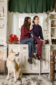 Joyeux jeune couple posant assis sur une commode avec un chien de race akita inu. dans les décorations de noël dans un style rétro