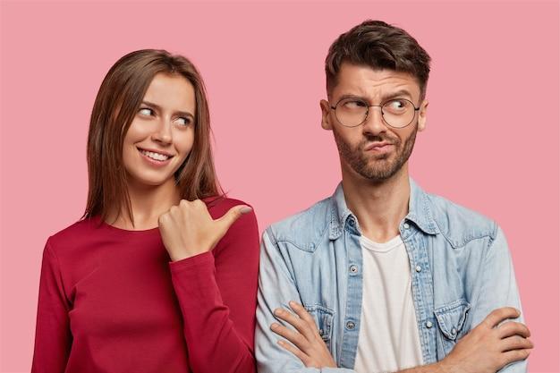 Joyeux jeune couple posant contre le mur rose