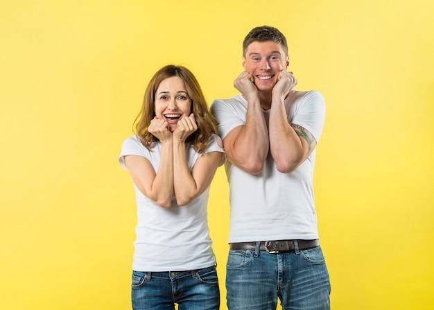 Joyeux jeune couple à la recherche d'appareil photo sur fond jaune