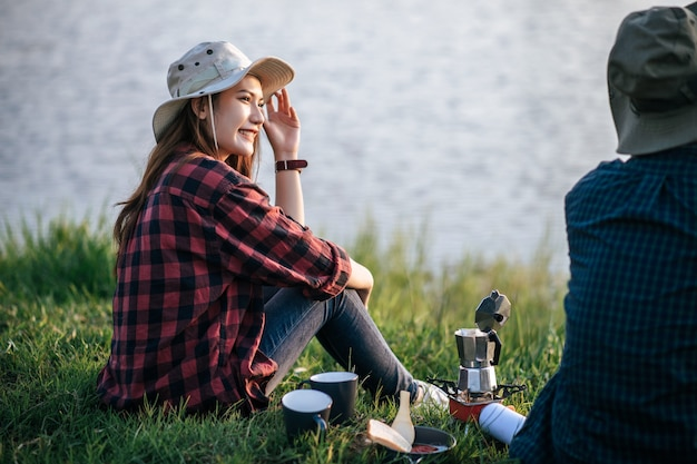 Joyeux jeune couple de routards assis sur l'herbe et impatient sur le lac tôt le matin et faisant un moulin à café frais pendant un voyage de camping en vacances d'été
