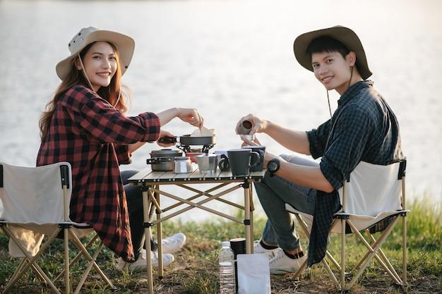 Joyeux jeune couple de routards portant un chapeau de trekking assis près du lac avec café et petit-déjeuner et faisant un moulin à café frais pendant un voyage de camping en vacances d'été