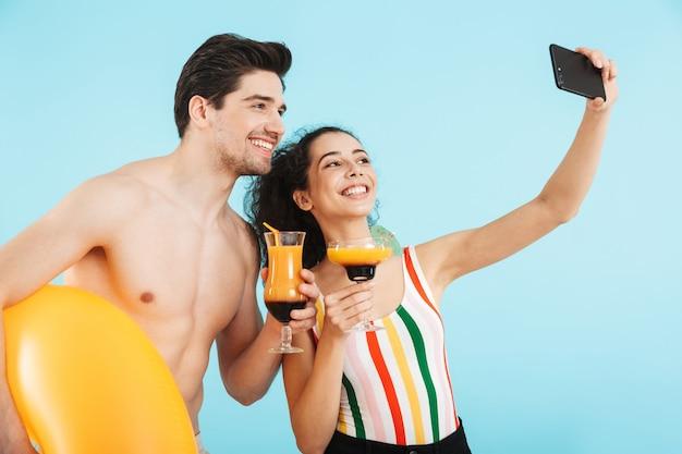 Joyeux jeune couple s'amusant à la plage avec un anneau gonflable isolé, buvant des cocktails, prenant un selfie