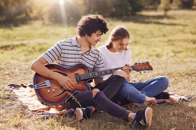Joyeux jeune couple s'amuser ensemble, chanter des chansons et jouer de la guitare, s'asseoir sur un plaid, avoir des expressions heureuses. attractive jeune homme bouclé joue de l'instrument de musique et divertit sa petite amie.