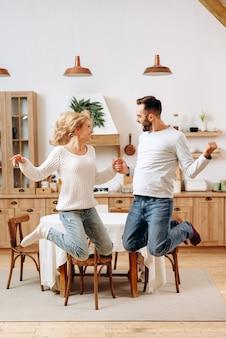 Joyeux, jeune couple se tenant la main dans l'appartement sautant de joie. mignons, les jeunes se réjouissent dans leur appartement