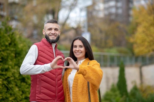 Joyeux jeune couple souriant tout en vous montrant le cœur
