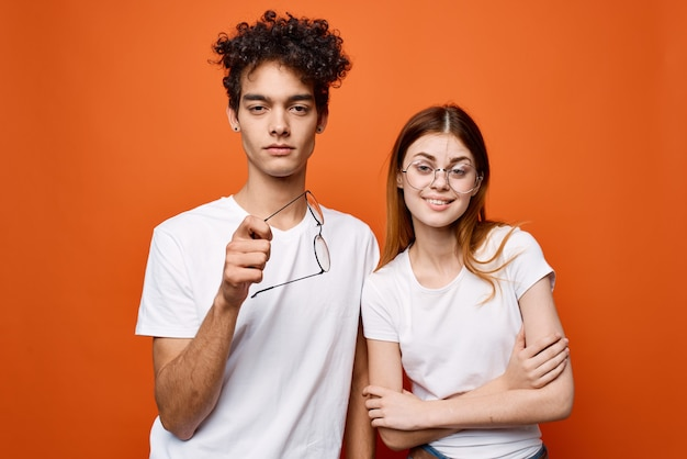 Joyeux jeune couple en t-shirts blancs discutant sur fond orange. photo de haute qualité