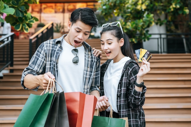 Joyeux jeune couple tenant plusieurs sacs à provisions en papier