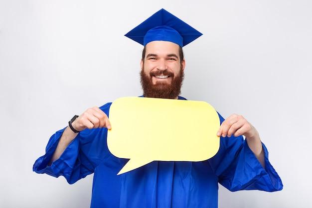 Joyeux jeune étudiant diplômé barbu tient une bulle de dialogue devant lui.