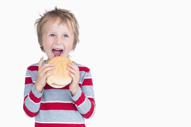 Joyeux jeune garçon mangeant un hamburger