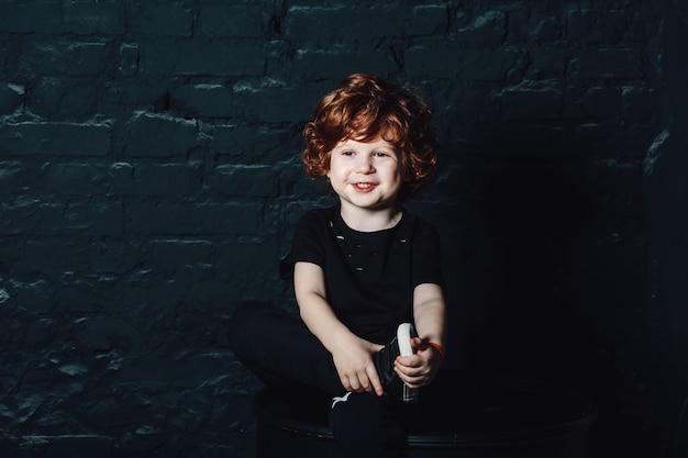 Joyeux jeune garçon à la recherche de suite et souriant.