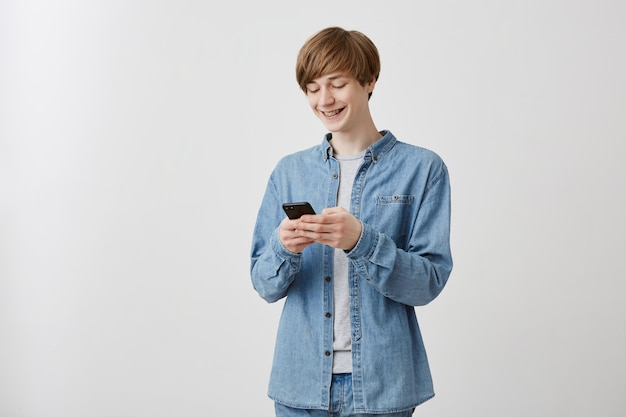 Joyeux jeune hipster caucasien aux cheveux blonds vêtu d'une chemise en jean sur un t-shirt gris jouant à un gadget électronique activé par le jeu vidéo sur internet. heureux mec souriant, surfer sur internet en utilisant le wifi sur téléphone portable