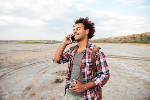 Joyeux jeune homme africain avec une vieille photo vintage devant debout et parlant au téléphone portable