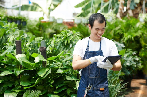 Joyeux jeune homme asiatique vérifiant des informations sur une tablette lorsqu'il travaille dans une pépinière