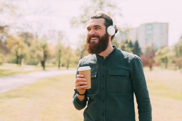 Joyeux jeune homme barbu souriant à l'extérieur, écoutant de la musique tout en tenant une tasse de café
