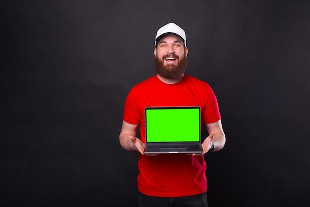 Joyeux jeune homme barbu souriant en t-shirt rouge et montrant un écran vert sur un ordinateur portable
