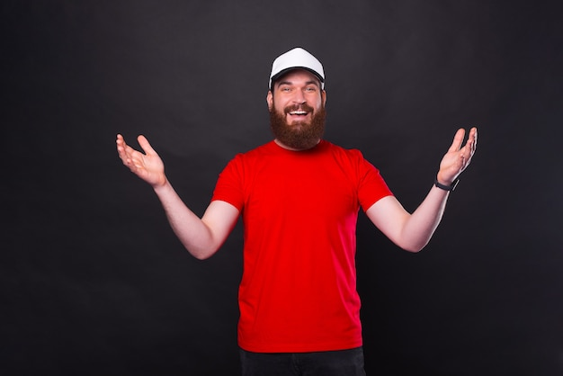 Joyeux jeune homme barbu en t-shirt rouge faisant un geste de bienvenue