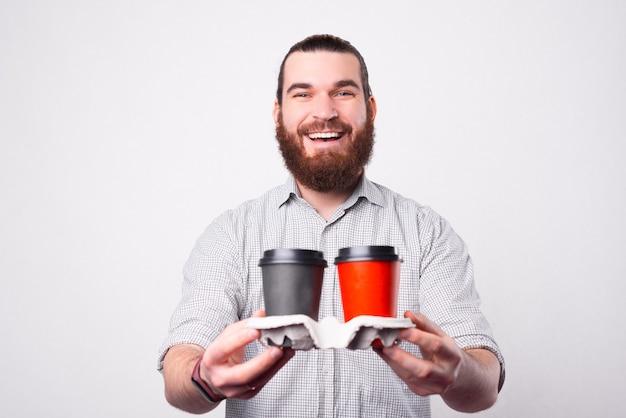 Un joyeux jeune homme barbu tient un ensemble de deux boissons chaudes dans des tasses de papper et en regardant la caméra sourit près d'un mur blanc