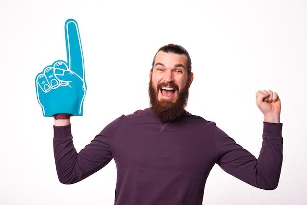 Joyeux jeune homme barbu tient un gant de ventilateur et regarde la caméra est excité