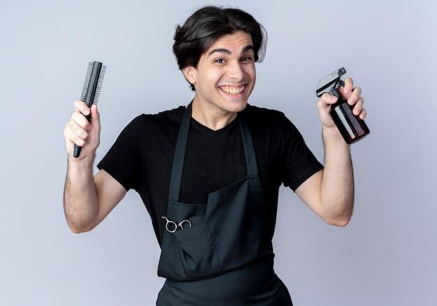 Joyeux jeune homme beau coiffeur en uniforme tenant peigne avec vaporisateur isolé sur fond blanc
