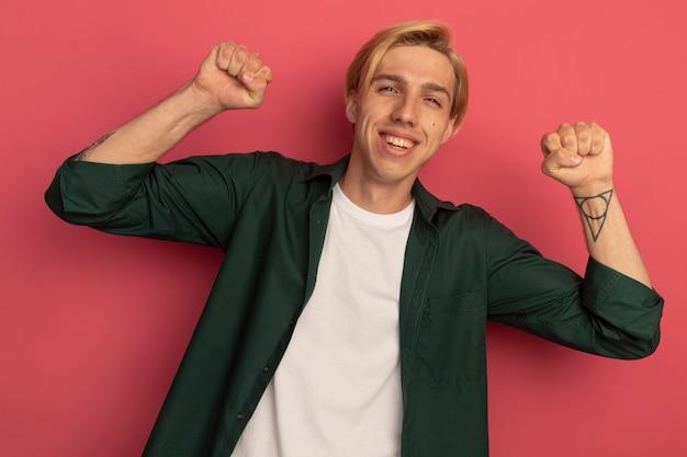 Joyeux jeune homme blond portant un t-shirt vert montrant le geste oui