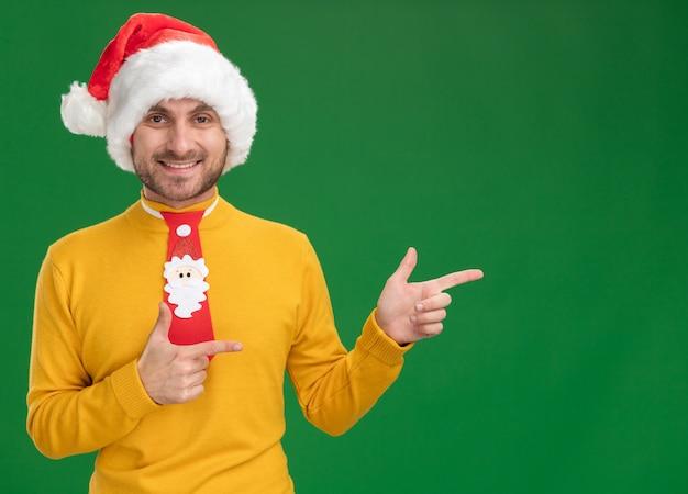 Joyeux jeune homme caucasien portant chapeau de noël et cravate regardant la caméra pointant sur le côté isolé sur fond vert