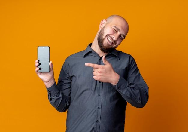 Joyeux jeune homme de centre d'appels chauve clignotant montrant un téléphone mobile et pointant sur il isolé sur orange