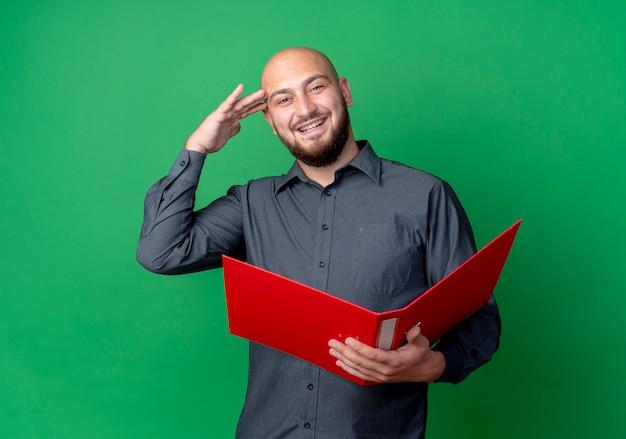Joyeux jeune homme de centre d'appels chauve tenant un dossier ouvert et faisant le geste de salut isolé sur vert