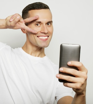 Joyeux jeune homme en chemise tenant un téléphone portable et faisant une photo de lui-même