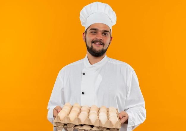 Joyeux jeune homme cuisinier en uniforme de chef tenant un carton d'œufs à la recherche d'isolement sur un mur orange