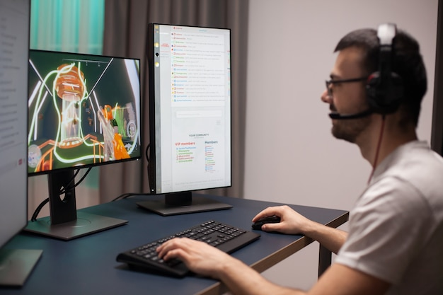 Joyeux jeune homme dans sa chambre jouant à des jeux vidéo en ligne sur ordinateur.