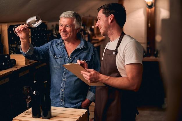 Joyeux jeune homme debout avec un presse-papiers dans une cave et regardant un verre de vin rouge à la main d'un collègue positif