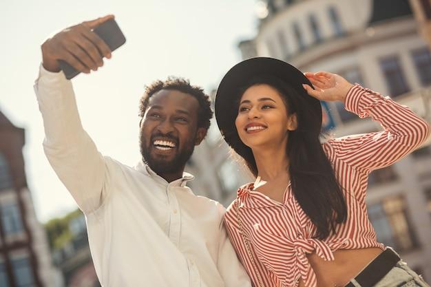 Joyeux jeune homme et femme debout à l'extérieur dans des vêtements d'été décontractés et souriant à la caméra du smartphone tout en prenant un selfie