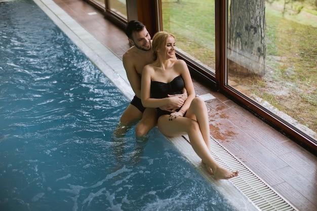 Joyeux jeune homme et femme se reposant au bord de la piscine dans un spa
