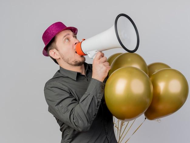 Joyeux jeune homme de fête portant un chapeau rose tenant des ballons et parle sur haut-parleur isolé sur blanc