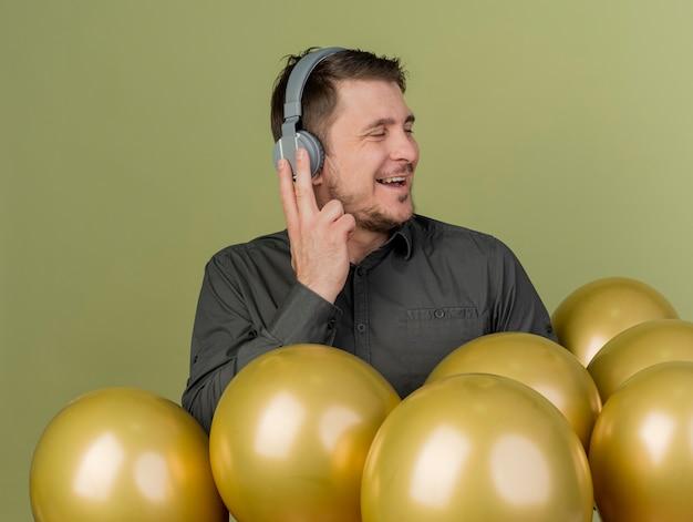 Joyeux jeune homme de fête portant une chemise noire et des écouteurs debout parmi les ballons isolés sur vert olive