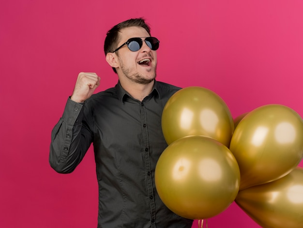Joyeux jeune homme de fête portant des lunettes tenant des ballons montrant oui geste isolé sur rose