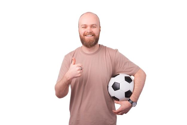 Joyeux jeune homme hipster avec barbe tenant un ballon de football et montrant le pouce vers le haut sur blanc