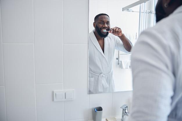 Joyeux jeune homme international portant un peignoir tout en se nettoyant les dents devant le miroir