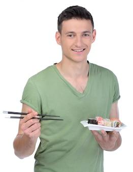 Joyeux jeune homme, manger des sushis en position debout.