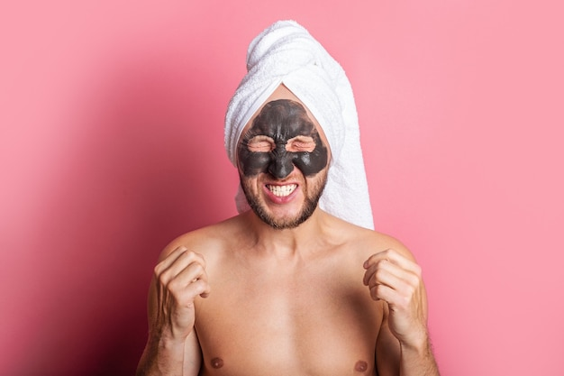 Joyeux jeune homme avec un masque cosmétique sur son visage, les yeux fermés sur fond rose.