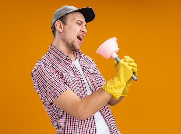 Joyeux jeune homme nettoyant portant une casquette avec des gants tenant un piston chantant isolé sur un mur orange