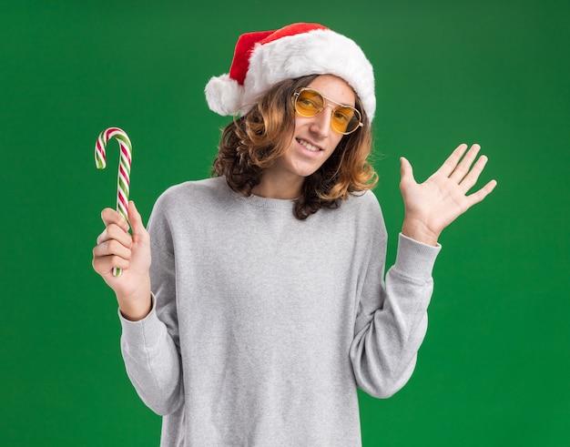 Joyeux jeune homme portant chapeau de père noël et lunettes jaunes tenant la canne en bonbon regardant la caméra souriant joyeusement avec le bras levé debout sur fond vert