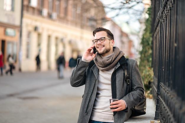 Joyeux jeune homme portant une écharpe parlant au téléphone et buvant du café dans la rue.