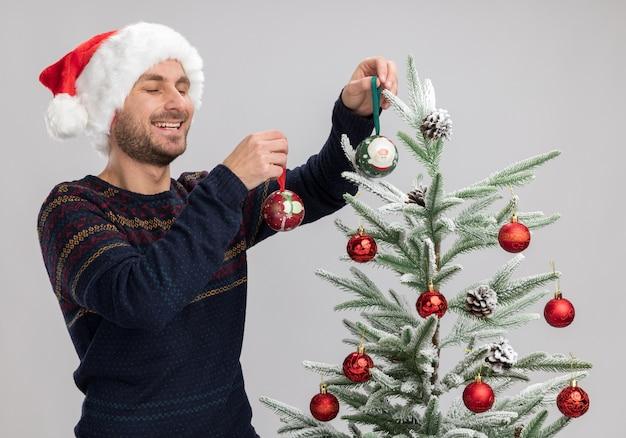 Joyeux jeune homme de race blanche portant un chapeau de noël debout près de l'arbre de noël en le décorant avec des boules d'ornement de noël en riant les yeux fermés isolé sur fond blanc