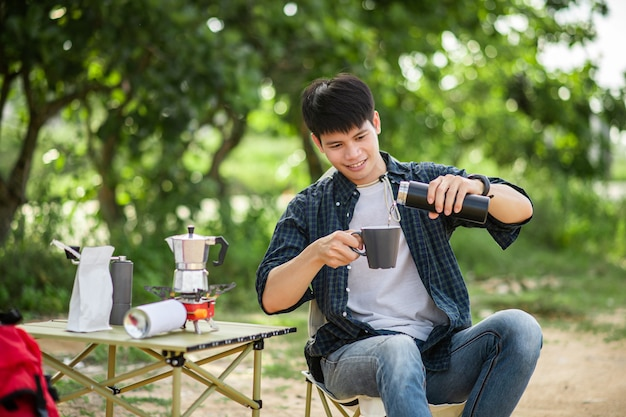 Joyeux jeune homme routard assis devant la tente dans la forêt avec un service à café et faisant un moulin à café frais lors d'un voyage de camping en vacances d'été